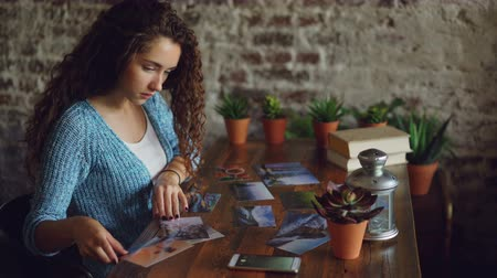 lays : Pretty girl creative designer is putting photographs on wooden table then shooting flat lay pictures with smartphone. Modern technology, illustrations and people concept.