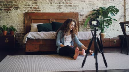 vlogging : Attractive young woman with long curly hair blogger is recording video for her internet blog using camera, girl is showing smartphone and photographs and talking. Stock Footage