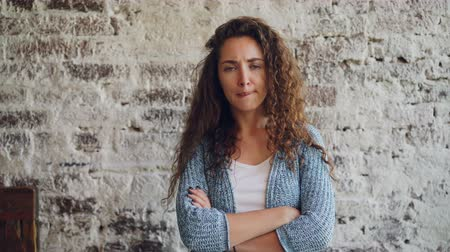crossed : Portrait of unhappy girl looking at camera, frowning and shaking head standing with crossed arms with brick wall in background. Emotions, feelings and people concept.