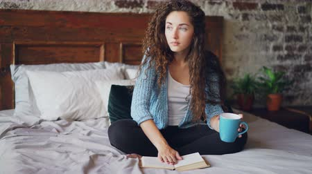 linen : Pretty girl reading book sitting on bed at home and holding cup with drink enjoying free time and resting. Young people, hobby and modern interior concept.