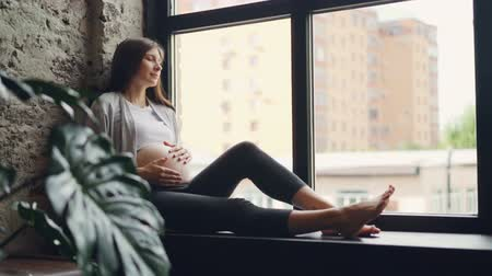 belly : Attractive pregnant lady is sitting on window sill and caressing her baby bump, she is looking outside then closing her eyes and resting. Modern interiors and pregnancy concept.