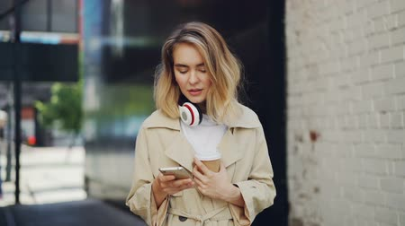 tomar : Slow motion of pretty young lady holding smartphone touching screen and drinking to-go coffee outdoors. Urban lifestyle, take away drinks and modern technology concept.