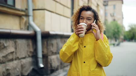 go away : Pretty African-American woman is drinking to-go coffee and chatting on mobile phone walking in the city in spring wearing bright jacket. Modern technology and millennials concept.