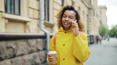 call out : Cheerful mixed-race teenage girl is talking on smart phone and holding take out coffee walking along street in beautiful city. Modern lifestyle and technology concept. Stock Footage