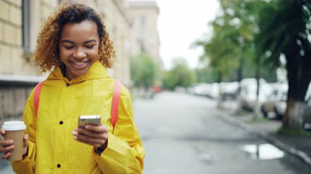 неформальный : Happy African American woman is using smartphone touching screen and smiling walking outdoors in beautiful city with to-go coffee. Modern lifestyle and communication concept.