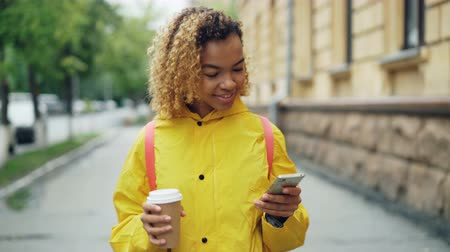 go away : Smiling African-American girl is using smartphone texting friends and holding to-go coffee walking in city alone. Modern technology, communication and drinks concept.
