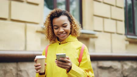 surfing the net : Attractive mixed race woman is using modern smartphone looking at screen and smiling surfing the net or watching photos and holding take away coffee standing outdoors.