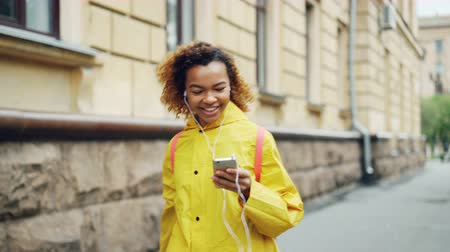 enjoyable : Young African American woman is listening to music through earphones and dancing walking along street in modern city wearing bright clothing. Fun and gadgets concept. Stock Footage