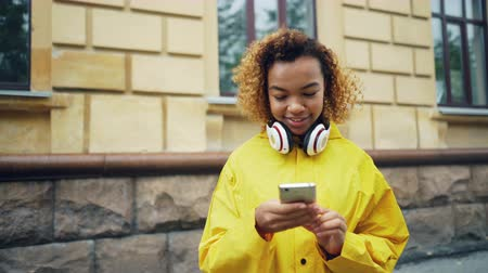 news stand : Happy African American student is using smartphone browsing or texting friends standing outdoors in the street of modern city wearing headphones and smiling. Stock Footage