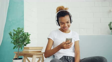 mensageiro : Happy African American woman is surfing internet with smartphone and laughing sitting on sofa at home, girl is listening to music through headphones.