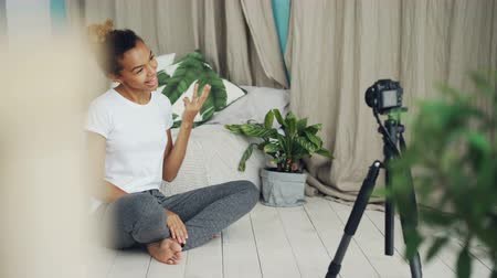 seguidores : Pretty African American teenager vlogger is recording video for social media followers, girl is looking at camera, speaking and gesturing sitting on bedroom floor.