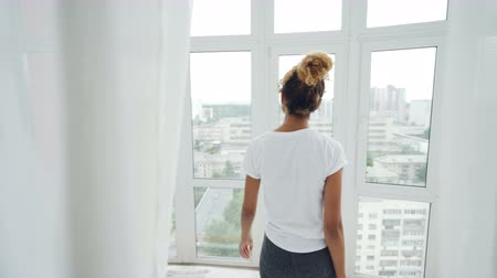 hátsó megvilágítású : Back view of African American woman walking to panoramic window, parting curtains and looking outside enjoying view of big modern city. Accommodation and people concept.