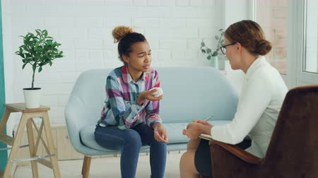 helpful : Unhappy mixed race girl is talking to psychologist and crying sitting on couch while doctor is listening to her holding paper and pen. Therapy, people and problems concept. Stock Footage