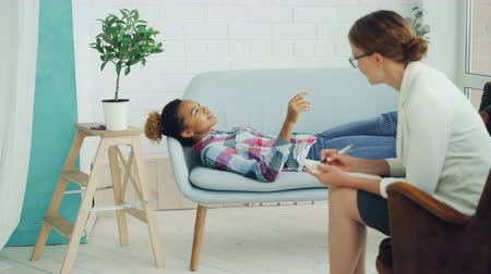 together trust : African American teenager is talking to psychologist lying on couch and smiling while therapist is listening and taking notes. Young people, mental health and profession concept. Stock Footage