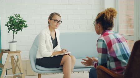 helpful : Confident female psychologist is holding consultation with African American girl, listening to her and writing while patient is speaking explaining problem.