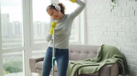 ev işi : Happy young blonde is doing housework and having fun in modern house, she is washing floor with mop, singing and dancing listening to the radio through headphones. Stok Video