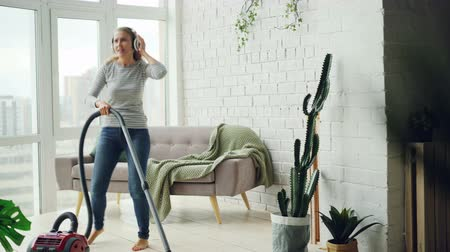 vácuo : Cheerful blond housewife is using vacuum cleaner during routine clean-up at home, listening to music through headphones, singing and dancing. Technology and people concept.