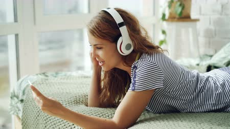 enjoyable : Cute young woman is listening to music in headphones and touching smartphone screen resting on bed at home. Technology, youth culture and interior concept.
