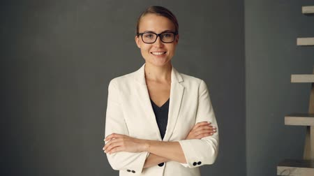 hanedan arması : Slow motion portrait of young businesswoman wearing formal clothing and glasses looking at camera and smiling. Confident people, youth and positivity concept. Stok Video