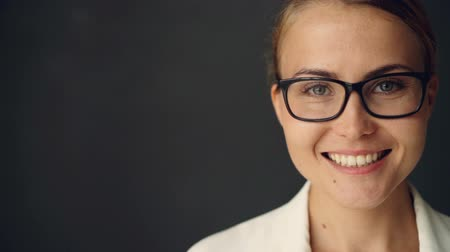 půvabný : Close-up slow motion portrait of cheerful businesswoman in glasses looking at camera with toothy smile against dark gray background. People, positivity and emotions concept.