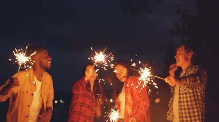 multiethnic : Slow motion of men and women dancing and jumping outdoors with burning sparklers, having fun, celebrating holiday and enjoying good company. People and entertainment concept. Stock Footage