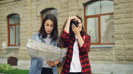 foreigner : Female tourist is taking photos while her friend attractive girl is looking at map and showing her direction standing in the street then walking away. Stock Footage