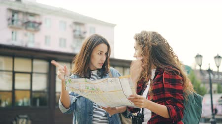 foreigner : Cheerful young women friends with backpacks are looking at map and talking standing together in beautiful town in the street and discussing right direction. Stock Footage
