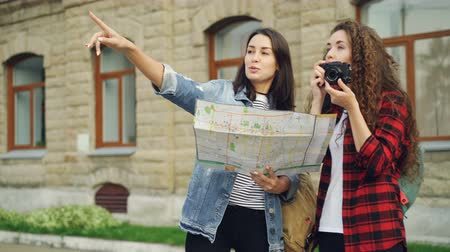 иностранец : Happy girls travelers are looking at map and taking photos with camera standing in the street together and talking. Photography, tourism and sightseeing concept. Стоковые видеозаписи