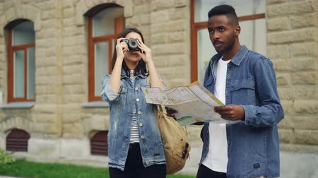иностранец : Handsome African American man traveler is looking at map when his attractive female friend is taking photos using camera standing in city center and talking.