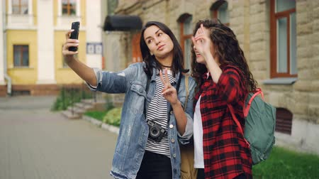 иностранец : Cheerful girls foreign travelers are taking selfie using smartphone standing outdoors and posing with hand gestures showing v-sign and heart with fingers and laughing. Стоковые видеозаписи