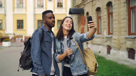 foreigner : Beautiful multiracial couple is talking with friends online making video call using smartphone standing in the street with backpacks. Travelling and technology concept.