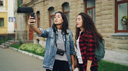 foreigner : Emotional young women travelers are making online video call using smartphone holding device and talking showing historical building behind them expressing excitement.
