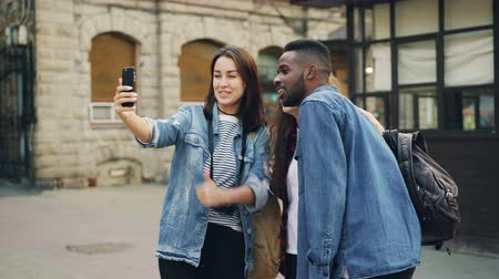 foreigner : Excited young people are making online video call using smartphone holding gadget and talking showing building behind them expressing positive emotions showing thumbs-up.