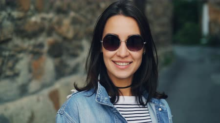 brim : Close-up slow motion portrait of cute girl with dark hair in stylish sunglasses standing outside with stone wall in background, smiling and looking at camera. Stock Footage