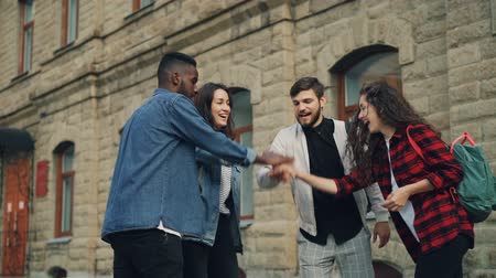 handen ineen : Slow motion of multiracial group of friends travelers putting palms together then raising arms in the air and laughing standing in the street. Friendship and unity concept. Stockvideo