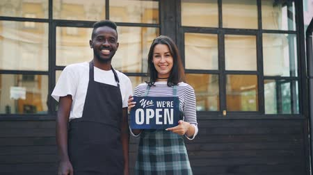 официант : Slow motion portrait of beautiful multiracial couple cafe owners standing outside with we are open sign smiling and looking at camera. Business, people and city concept.