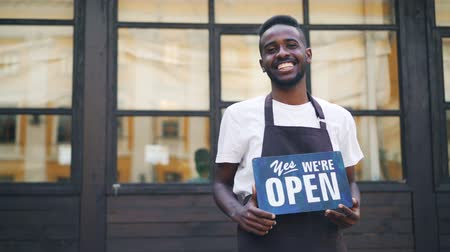 proprietário : Slow motion portrait of African American guy urban cafe owner posing with we are open sign standing outdoors and looking at camera. Local business and millennials concept.