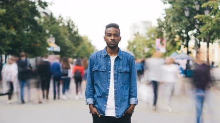 outsider : Time-lapse portrait of African American man in casual clothes looking at camera standing in busy street downtown suffering from loneliness when people are passing by.