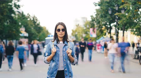outsider : Time-lapse portrait of confident young lady in sunglasses standing in city center among running people and resting looking at camera. Time and youth concept.