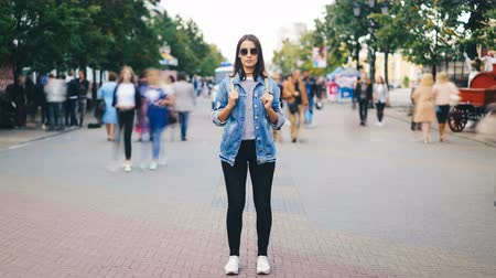 outsider : Time-lapse of attractive young woman wearing sunglasses standing alone in big city with backpack and looking at camera when crowds of people are passing by.