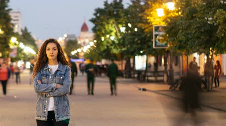бросаясь : Time-lapse of unhappy girl standing alone on beautiful pedestrian street late in the evening and looking at camera when people are whizzing around. Society and loneliness concept. Стоковые видеозаписи