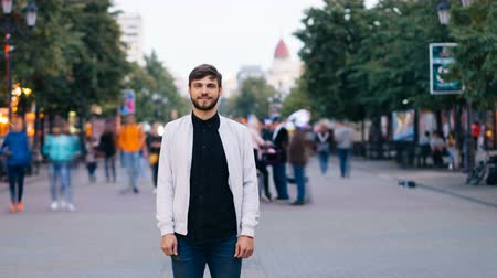 бросаясь : Time-lapse of confident man in jeans and white jacket standing alone in street in city and looking at camera while people are rushing by on autumn day. Стоковые видеозаписи