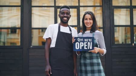 começando : Slow motion portrait of man and woman business partners holding cafe open sign and smiling looking at camera. Starting business and success concept.