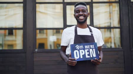 slate : Slow motion portrait of cheerful African American businessman cafe owner holding we are open sign standing outside and looking at camera. Small business and youth concept.