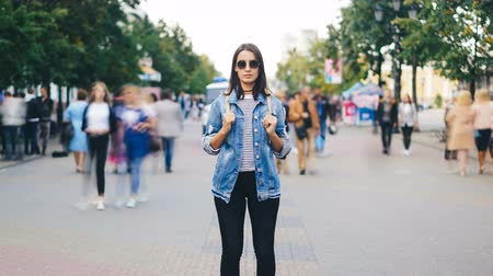 outsider : Zoom in time-lapse of female traveler standing in the street with backpack wearing sunglasses and casual clothing and looking at camera when men and women are rushing around.