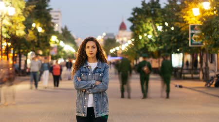 outsider : Time-lapse portrait of lonely young lady standing in street downtown with arms crossed while crowds of men and women are passing by. Loneliness and time concept.