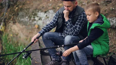 paternal : Serious little boy is catching fish with his father bearded brunet sitting together and holding fishing rods. Common hobby, generations and family concept. Stock Footage