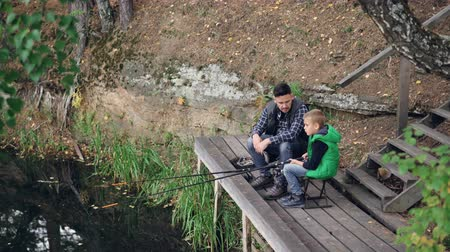 paternal : Little boy is fishing in lake with his daddy from wooden pier on autumn day, child is holding rod sitting on chair while his father is talking to him. Nature and people concept.