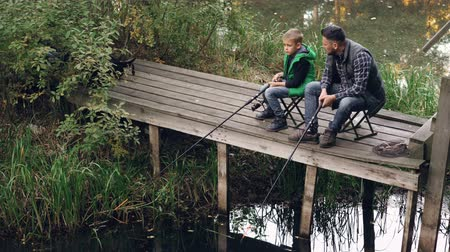 otcovství : Good-looking man and his cute son are fishing in pond from wooden dock sitting on chairs with rods and talking. Loving family, common hobby and generations concept.