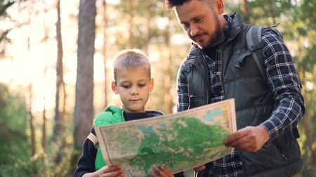 オリエンテーション : Slow motion of happy family father and cute son looking at map and talking during hike in forest in autumn. Trees, sunshine and backpacks are visible.